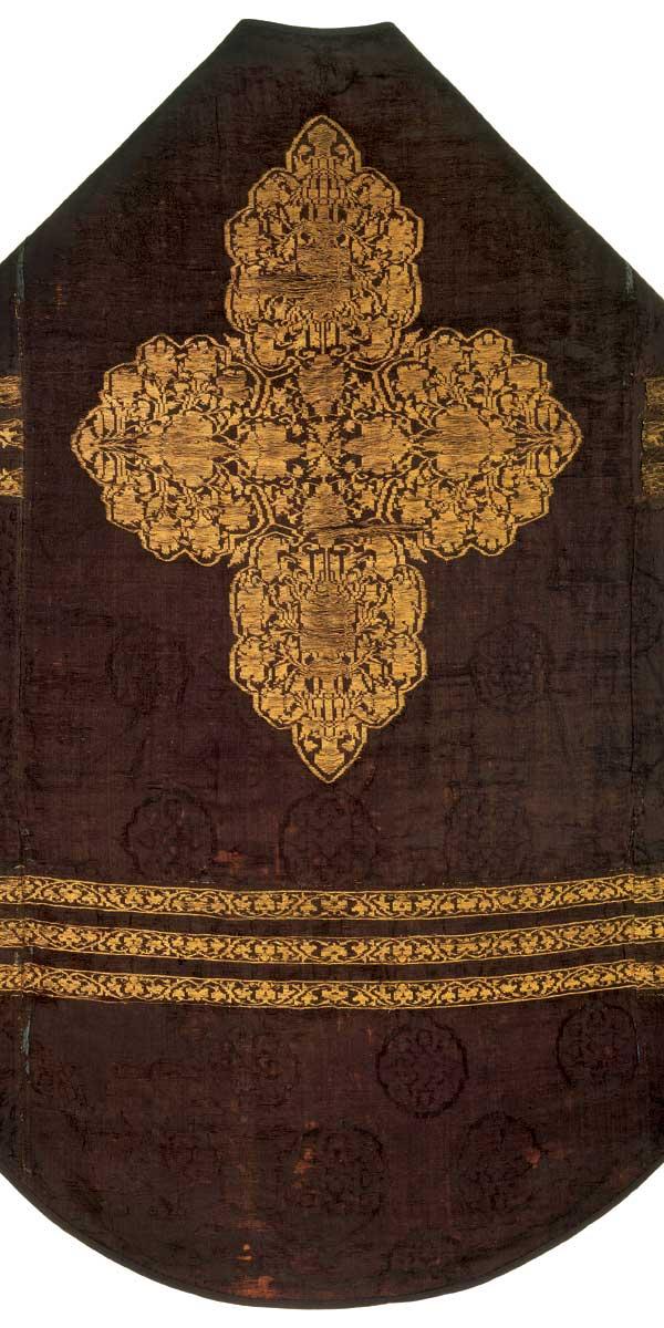 M 29 Kasel aus schwarz-brauner Seide mit eingewebtem, goldbroschiertem Vierpassmotiv und Rankenbändern, Iran (?), 14. Jh., H. 141 cm, B. 69 cm. Die Komposition ist das Ergebnis eines geschickten Zuschnitts einzelner Stoffteile. Foto: Walter Haberland.