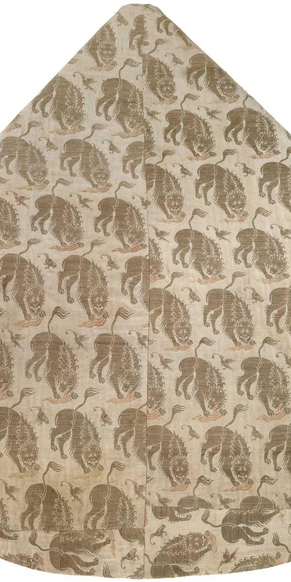 M 42 Kasel aus weißer Seide mit Löwen, Italien, spätes 14. Jh., H. 130,5 cm, B. 95 cm. Bei genauem Hinsehen erkennt man, dass sich die Tiere von der einen zur anderen Reihe in der Kopfhaltung unterscheiden. Eine Lupe offenbart zudem die Zunge, mit der sie aus einer Blutlache trinken. Beides ist in roter Seide hervorgehoben; ein Beispiel für ihre meisterhafte Detailtreue, in der die Muster der Stoffe gewebt wurden. Foto: Walter Haberland.