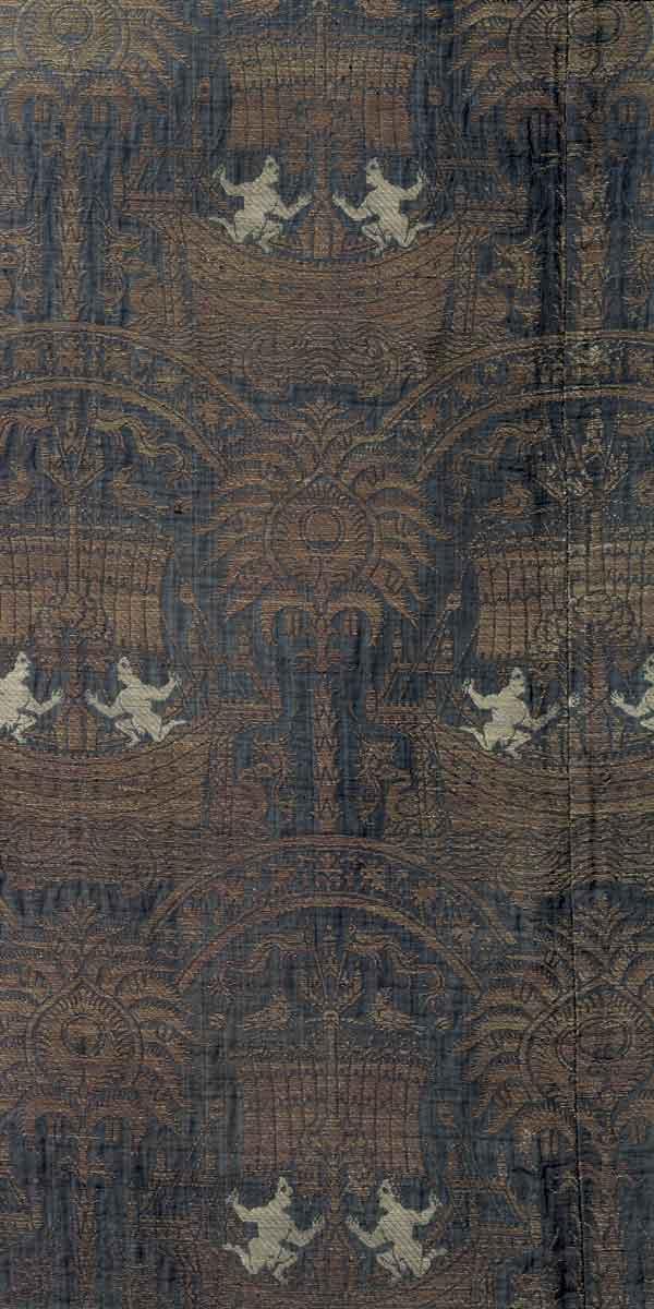 M 43 Kasel aus blauer Seide mit Segelschiffen, Italien, spätes 14.Jh., H. 138 cm, B. 116 cm. Die Kasel befindet sich im Germanischen Nationalmuseum (GNM). Ausschnitt hier ebenfalls wegen seiner Detailtreue aufgenommen. Auf dunkelblauem Grund zeigt das goldgewebte Muster eine der bemerkenswertesten Kompositionen, die aus der italienischen Seidenweberei des späten 14. Jahrhunderts überliefert sind. Die Takelage der Segelschiffe, die Eroten (?), die im Meer spielenden Wesen und vieles mehr; wiederum zeigt die Lupe eine wunderbare Welt – die Dank vorzüglicher Fotografie auch im Buch sichtbar bleibt. Foto: Jürgen Musolf – Monika Runge (GNM).