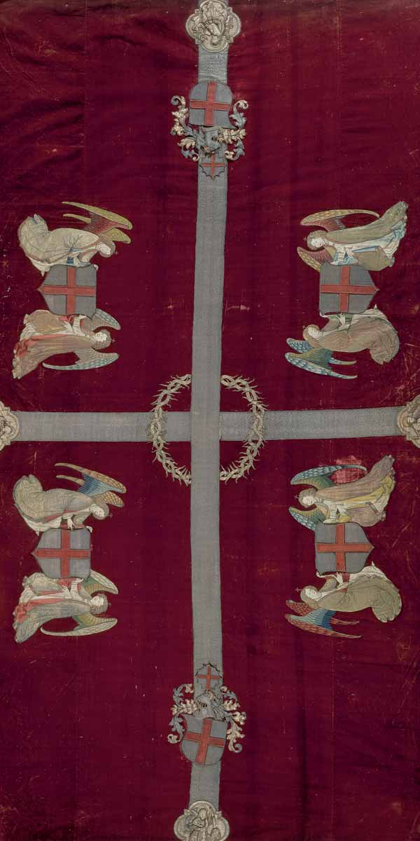 M 366 Sargdecke der Georgenbruderschaft, Seidensamt, Italien, 3. Viertel 15. Jh., Stickerei Südliche Niederlande (?), spätes 15. Jh., H. 375 cm, B. 221 cm. Die prominentere von zwei im Schatz erhaltenen Sargdecken, die aus vier leuchtend roten Seidensamtteilen zusammengefügt ist. Die Mitte überspannt ein mit Silberfäden aufgesticktes Kreuz, dessen Zentrum von einer Dornenkrone umfangen wird. An den Enden der Kreuzarme befinden sich Medaillons, in denen die vier Evangelisten dargestellt sind. Auf dem Längsbalken des Kreuzes liegen davor die Abbildungen der Wappen der Georgenbruderschaft; sie kehren, von Engeln gehalten, in den vier Stoffteilen der Decke wieder. Diese große Tuch wurde nur bei Totenfeiern besonders wichtiger Angehöriger der Bruderschaft verwendet, das weniger reich ausgestattete (M 367) bei der Bestattung anderer Mitglieder. Foto: Walter Haberland.